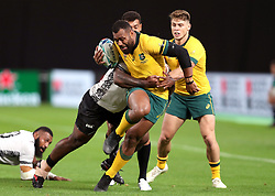 Australia's Samu Kerevi (centre) is tackled by Fiji's Peni Ravai (left) during the 2019 Rugby World Cup Pool D match at Sapporo Dome.