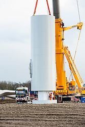 Ulley Wind Farm making the lorry that brought it onto the site look like a child's toy the first of the four sections that make up the turbines tower is lifted into place.note the workmen in orange ensuring the correct position of the section before it is finally lowered into place...13  March  2013.Image © Paul David Drabble