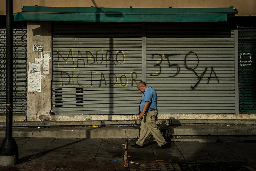 """CARACAS, VENEZUELA - JULY 27, 2017: A man walks past a shop closed in support of a national strike, that has graffiti painted on its security door that says, in Spanish: """"Dictator Maduro"""" and """"350 Now"""" - the article in the constitution that allows for civil disobedience against tyranny. The political opposition called for a 48 hour national strike for July 26th and 27th, and for their supporters to close businesses, not go to work, and instead create barricades to block off their streets.  Opposition controlled areas of the country were completely shut down.  The strike was called as part of the opposition's civil resistance movement - that began on April 1st, to protest against the Socialist government's attempt to elect a new constituent assembly that will have the power to re-write the constitution, and will threaten democracy.  PHOTO: Meridith Kohut for The New York Times"""