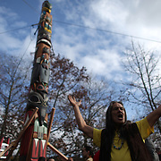 Native carver Saaduuts throws up his arms as a totem pole is erected at the Seattle Center on Sunday February 26, 2012 in Seattle. The 33-foot tall totem pole was erected Sunday in honor of slain Native American woodcarver John T. Williams. Williams was shot and killed by a Seattle Police officer in 2010. The shooting was later ruled unjustified.  (Joshua Trujillo, seattlepi.com)