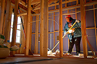 NC State volunteer sweeps upstairs in one of the townhouses while working on the Build-A-Block Habitat for Humanity project.