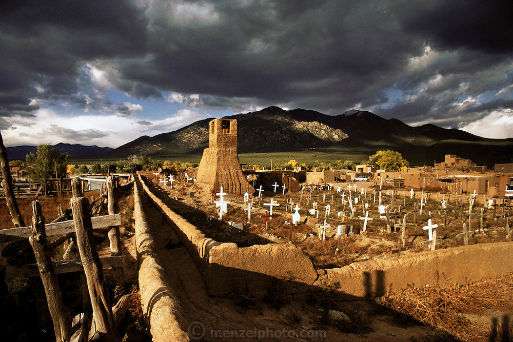 Taos Pueblo cemetery with approaching storm clouds, New Mexico, USA.