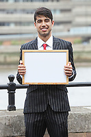 Portrait of young Indian businessman holding blank sign