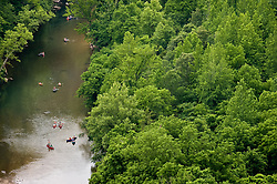 Paddlers enjoy a leisurely float down the Buffalo River in Arkansas. The view is from Big Bluff which is part of the Buffalo National River. Big Bluff is accessed from a side trail off the Center Point Trail.<br /> <br /> The 150-mile Buffalo River in northern Arkansas was the first river in the United States to receive the designation as a National River. The Buffalo National River, encompasses 135 miles of the river which is managed by the National Park Service. The river is a popular canoeing, kayaking, camping, and fishing destination. Popular destinations in the national river's boundaries include; Lost Valley, Hemmed-Iin-Hollow Falls (the highest waterfall between the Appalachian and Rocky Mountains, Indian Rockhouse, numerous caves and over 500-foot tall bluffs. The area is also home to Arkansas' only elk herd.