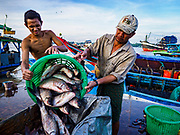 23 NOVEMBER 2017 - YANGON, MYANMAR: Workers unload fish from the cargo hold of a boat at the San Pya Fish Market. San Pya Fish Market is one of the largest fish markets in Yangon. It's a 24 hour market, but busiest early in the morning. Most of the fish in the market is wild caught but aquaculture is expanding in Myanmar and more farmed fresh water fish is being sold now than in the past.    PHOTO BY JACK KURTZ