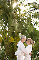 Middle-aged couple standing by palm trees embracing