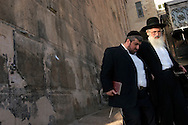 Rabbis pass by the wall of the Tomb of the Patriarchs (Ma'arat HaMachpela) where for 700 years Jews were not allowed to climb past the seventh step. Today Jews have access to part of the ancient site except for tens days of the year when they can worship in the entire building. The rest of the site is used as a mosque for Muslim worshipers...Hebron, Israel. 31/10/2007..Photo © J.B. Russell/Blue Press