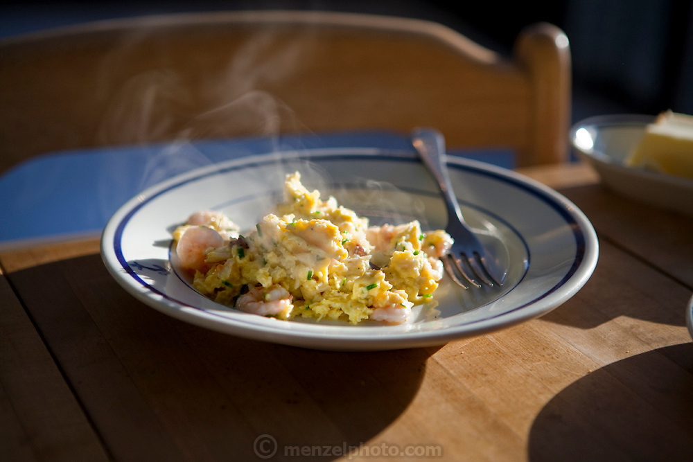 Lobsterman Samuel Tucker's breakfast of fresh shrimp and eggs. (From the book What I Eat: Around the World in 80 Diets.) The caloric value of his day's worth of food in March was 3,800 kcals. He is 50; 6 feet 1 and 1/2 inches and 179 pounds.