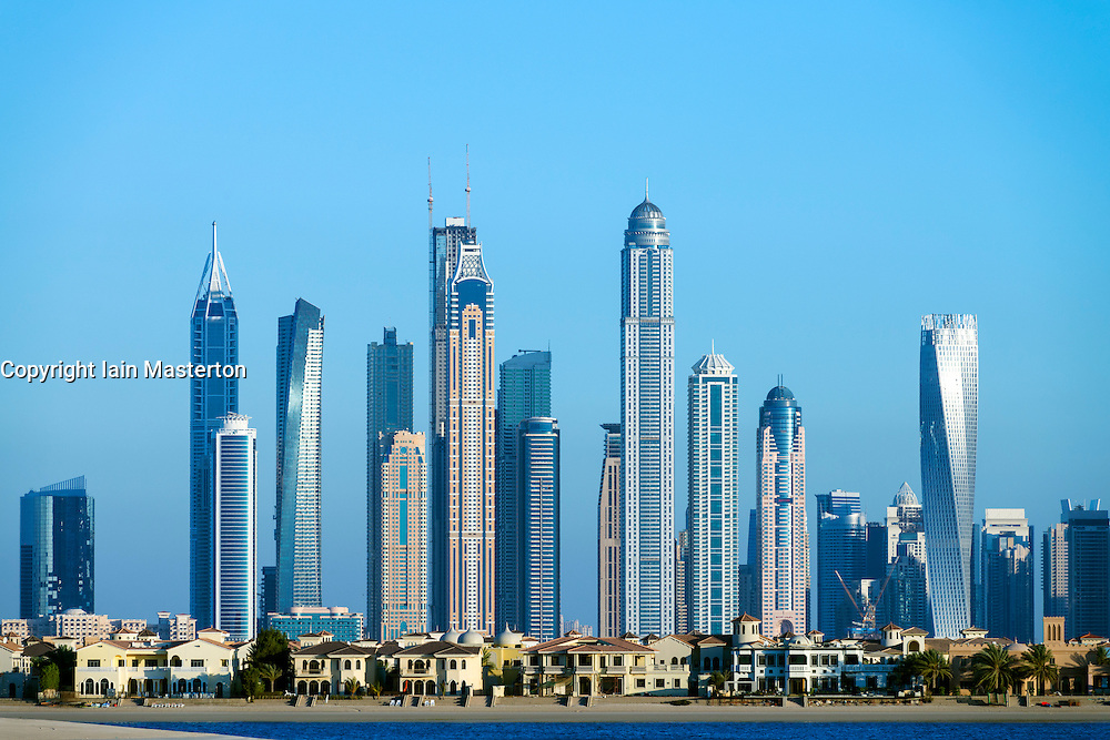 Skyline of Dubai apartment skyscrapers contrasting with luxury villas on The Palm Island in United Arab Emirates