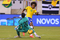 Sep 9, 2014; East Rutherford, NJ, USA; Brazil midfielder Willian (19) scores a goal on Ecuador goalkeeper Alexander Dominguez (22) during the first half at MetLife Stadium.