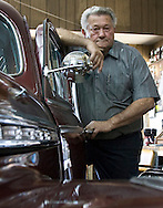 Mel Potts stands next to his '41 Chevy he rebuilt Wednesday at the shop he co-owns, Bob's Auto Repair. (Photo by Evert Nelson/Salina Journal)