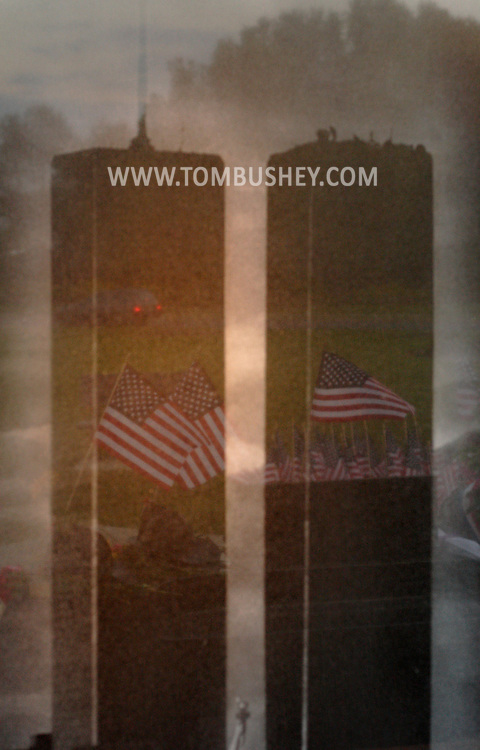 Washingtonville, N.Y. - American flags are reflected in an image of the Twin Towers on the monument at the Washingtonville 5 Firefighters World Trade Center Memorial before a candlelight service on Sept. 11, 2008. The Memorial was built in honor of five FDNY firefighters from Washingtonville and the many others who lost their lives on September 11, 2001 in the World Trade Center terrorist attack.