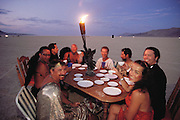 A dinner table is set in the desert at Burning Man in the late afternoon. Later that evening, 8 celebrants have dinner, and then burn the table. A group of San Francisco friends brought a table and chairs from a yard sale, had dinner in the desert near the Burning Man, then burned the dining set Burning Man is a performance art festival known for art, drugs and sex. It takes place annually in the Black Rock Desert near Gerlach, Nevada, USA.