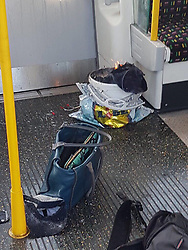 BREAKING NEWS: Several people are injured as explosion on Tube train in west London sends 'fireball flying down the carriage' setting commuters on fire as armed police race to the scene..Terrified commuters 'ran for their lives' after an explosion on a London Underground train this morning..People fled in panic and jumped out train doors after a 'fireball flew down the carriage', leaving several passengers with serious facial burns on the packed rush hour train in Parsons Green, west London..There were reports of a man at the station with a knife in the aftermath of the explosion. Scotland Yard said they believe this is unrelated to the Tube incident but are investigating and urging people to avoid the area..One witness told the BBC there was a 'bang' and then a 'wall of flames', which spread through the packed carriage. .The doors opened at Parsons Green and the commuters, many of them with scorched faces and hair, ran off screaming..Armed Police, paramedics and firefighters were all said to be at the west London station within five minutes of the explosion at 8.20am today. .Pictures from the District Line train show a burning plastic bucket stashed in a Lidl carrier bag, which is said to have exploded and sent a fireball down the carriage..A photograph of the flaming white bucket taken just after it exploded shows a number of wires protruding out of the top and on to the train carriage floor - but police have not yet confirmed if it was a bomb..©Exclusivepix Media (Credit Image: © Exclusivepix media via ZUMA Press)