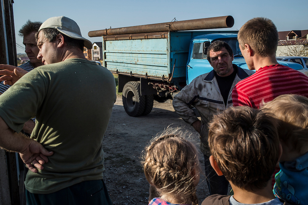 A group of internally displaced people who fled the besieged city of Donetsk discuss how to unload a large pipe needed to install a heating system for the small seaside resort that has become their home on Tuesday, October 14, 2014 in Berdyansk, Ukraine. Photo by Brendan Hoffman, Freelance