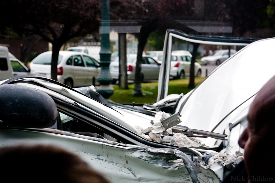Santiago, Chile 2010<br /> <br /> Passengers look at damage to a car being hauled away two weeks after the 7.7 earthquake that struck just outside the capital of Santiago.