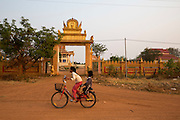 Two children on a bicycle pass the entrance to the village temple on a street in the village of in Banteay Char, near Battambang, Cambodia.