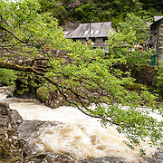 Betws-y-Coed River Rapids Snowdonia. The Afon Llugwy (River Llugwy) rapids flowing through Betws-y-Coed after particularly heavy rainfall. Betws-y-Coed is a small village in the heart of the Snowdonia National Park that is a popular base for hikers.