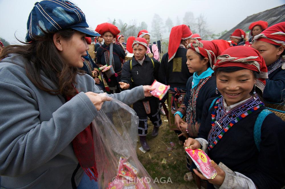 Hilltribe villages around Sapa. Vietnamese businesswoman distributing goods to Red Dzao women.