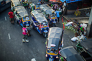 "26 SEPTEMBER 2012 - BANGKOK, THAILAND:  Tuk-tuks (three wheeled taxis) wait for fares at an exit to Khlong Toey Market in Bangkok. Khlong Toey (also called Khlong Toei) Market is one of the largest ""wet markets"" in Thailand. The market is located in the midst of one of Bangkok's largest slum areas and close to the city's original deep water port. Thousands of people live in the neighboring slum area. Thousands more shop in the sprawling market for fresh fruits and vegetables as well meat, fish and poultry.    PHOTO BY JACK KURTZ"