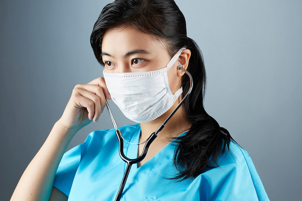 A portrait series representing the intense emotions that Doctors face.  An Asian female Doctor wearing a white surgical mask, stethoscope, and blue medical scrub suit shown.