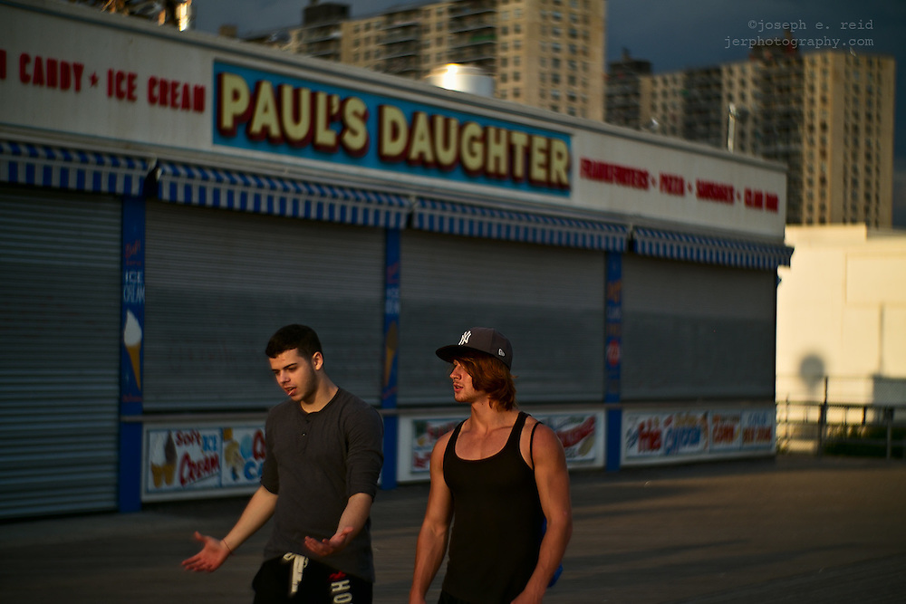 Two young men walking and talking on Coney Island boardwalk, Brooklyn, NY, US