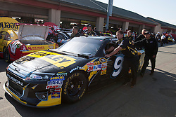 June 25, 2011; Sonoma, CA, USA;  Crew members push the car of NASCAR Sprint Cup Series driver Marcos Ambrose (not pictured) through the garage area during practice for the Toyota/Save Mart 350 at Infineon Raceway.