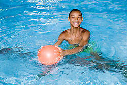 Boy playing with a ball during a game in the swimming pool at his local leisure centre,