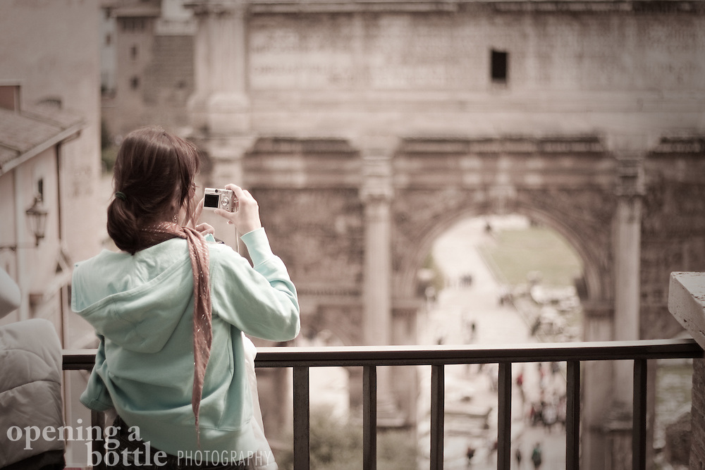 A tourist takes a picture of the Arch of Septimius Severus and the Roman Forum, Rome, Lazio, Italy. Full color image available upon request.