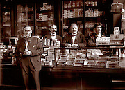 Vintage Photo: Men in the interior of a tobacco store circa 1910 Cigars fill the display case in foreground.
