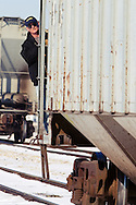 Riding a cut of grain hoppers pulled from the local elevator, a Kankakee, Beaverville & Southern Railroad conductor watches ahead.
