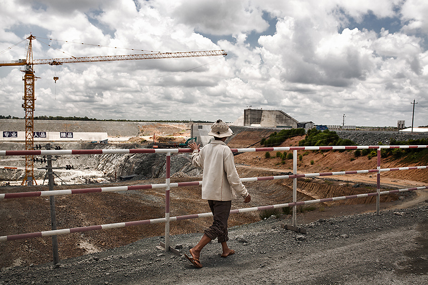 A fisherman walks along the fence inside the Lower Sesan 2 dam construction site. <br /> The dam, located only 1.5 Km below the confluence of the Sesan and Srepok river, will create a 36.000-hectares reservoir behind its wall, displacing around 5000 people and impacting the livelihood of 100.000 throughout the whole sub-Mekong region. The villagers of Phluk, located only 11 Km downstream, have witnessed a dramatic drop in fish since the dam construction began in 2013. <br /> &quot;They use calcium carbide for drilling and this made the water unsuitable for fishes&quot; - says Bun Aeng, a 50 year-old fisherman from Phluk, Stung Treng district, Northern Cambodia.