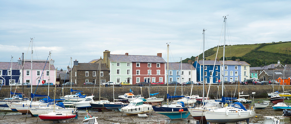 Pleasure boats - powerboats and yachts in harbour - bright painted harbourside housing at low tide in Aberaeron, Pembrokeshire, Wales, UK