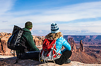 A man and woman sitting on the edge of a canyon wall looking out over the beautiful landscape of Canyonlands National Park and the La Sal Mountains, Utah, USA.