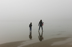 © Licensed to London News Pictures. <br /> 08/05/2016. <br /> Saltburn by the Sea, UK.  <br /> <br /> A mother and son walk across wet sand as heavy fog shrouds the coastline at Saltburn by the Sea in North Yorkshire as much of the country enjoys the hottest temperatures of the year so far.<br /> <br /> Photo credit: Ian Forsyth/LNP