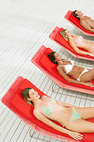 Young women and man sunbathing on deckchairs high angle view