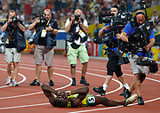 epa01459586 Usain Bolt of Jamaica is surrounded by photographers and TV cameramen as he lies on the track in jubilation after winning the men's 200m final and setting a new world record, at the Beijing Olympic games, Bird's Nest,  Beijing, China, 20 August 2008.  EPA/NIC BOTHMA