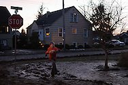 (Gabe Green   The Daily World)<br /> <br /> Take Dayton, 7, runs along a mud covered sidewalk Tuesday evening in his neighborhood in Aberdeen while his other siblings and mother are busy shoveling off the sidewalk.