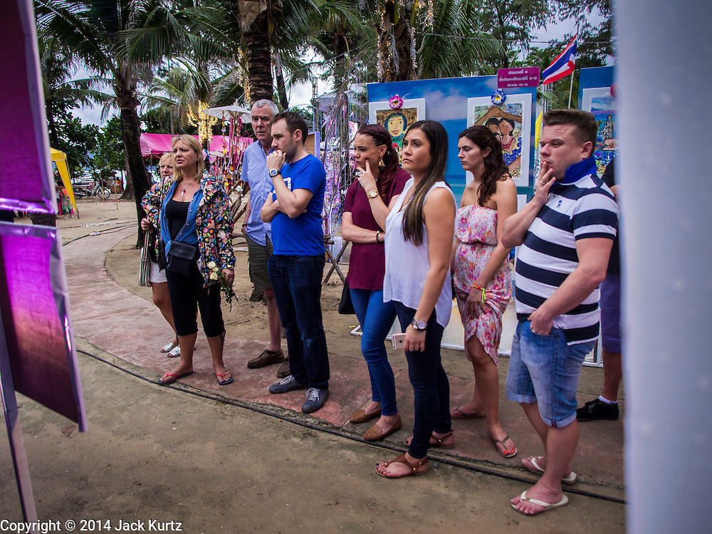 26 DECEMBER 2014 - PATONG, PHUKET, THAILAND: Tourists look at a display about the 2004 tsunami during services to mark the 10th anniversary of the 2004 tsunami in Patong, Phuket. Hundreds of people died in Patong and nearly 5400 people died on Thailand's Andaman during the 2004 Indian Ocean Tsunami that was spawned by an undersea earthquake off the Indonesian coast on Dec 26, 2004. In Thailand, many of the dead were tourists from Europe. More than 250,000 people were killed throughout the region, from Thailand to Kenya. There are memorial services across the Thai Andaman coast this weekend.    PHOTO BY JACK KURTZ