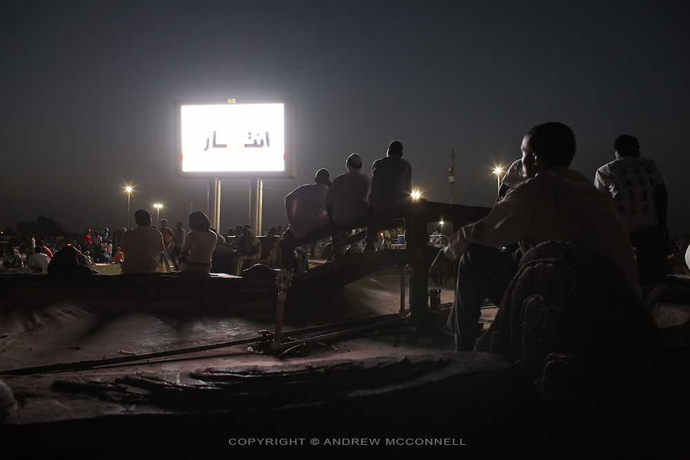 Locals gather under the glare of the new giant screens which line Khartoum's main transport route to and from the airport, in Sudan..Khartoum is modeling itself as the Dubai of Africa and despite Western sanctions the city is booming. Away from the troubles and poverty that plaque the rest of Sudan, development in Khartoum is moving at an astonishing rate. Investment from the East, and in particular China, allowed the Sudanese economy to grow by 11% in 2007. This growth is driven largely by oil, with production rising from 63,000 barrels per day in 1999 to over 500,000 barrels today.