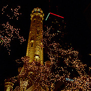 The Chicago Water Tower with the John Hancock Building in the background with red and green lights at the top for Christmas. Christmas Lights light the trees along the street near Michigan Avenue along a section know as the Magnificent Mile.
