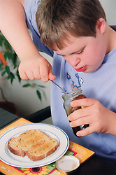 Teenage boy with Downs Syndrome sitting at breakfast table in front of slice of toast using knife to reach marmalade in jar,