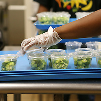 Lauren Wood   Buy at photos.djournal.com<br /> Lakesha Culpepper places portioned broccoli cups onto a tray with made-from-scratch ranch dressing Friday morning at Tupelo High School. In addition to serving students protein, bread, milk, and servings of fruit and vegetables, the school district is also required to serve one dried bean, one dark green vegetable and one orange vegetable a week.