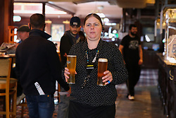 © Licensed to London News Pictures. 04/07/2020. London, UK. A staff member with glasses of drinks at THE TOLL GATE, a Wetherspoon pub in north London which reopened on Super Saturday. Cafes, restaurants, pubs and hairdressers across the UK closed on 23 March following the coronavirus lockdown. As restrictions are eased, cafes, restaurants, pubs and hairdressers reopens today. Photo credit: Dinendra Haria/LNP