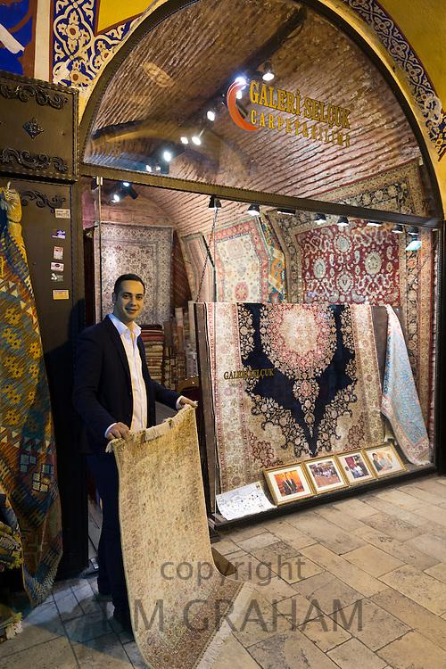 Salesman with traditional Turkish carpet rug in The Grand Bazaar, Kapalicarsi, great market, Beyazi, Istanbul, Republic of Turkey
