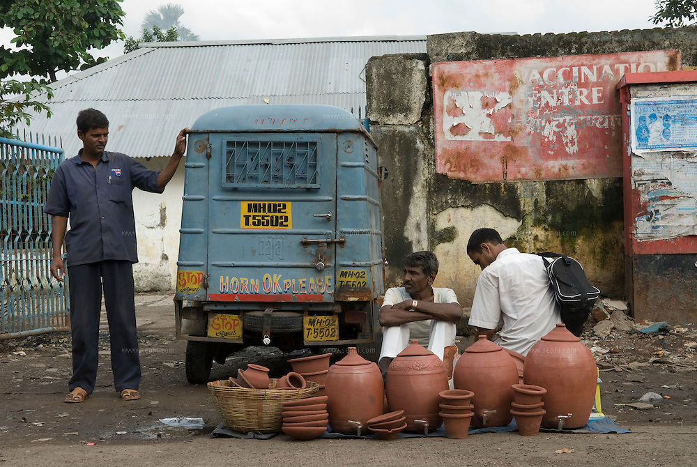 A potter sells his wares on the main road in dharavi. The Kumbhar potter community were the first to come to Dharavi from Gujarat as early as 1930.