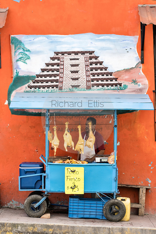A Mexican food vendor sells fresh chickens under a mural of the El Tajin pyramid outside the central Market in Papantla, Veracruz, Mexico.