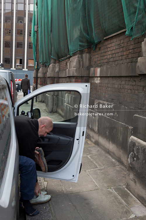 A driver changes shoes in his van outside a closed section of the former Smithfield meat market that is awaiting future redevelopment, on 20th November 2019, at Smithfield in the City of London, England. In March 2015, the Museum of London revealed plans to vacate its Barbican site and move into the General Market Building. The cost of the move is estimated to be in the region of £70 million and, if funding can be achieved, would be complete by 2021. There has been a market on this location since the Bartholomew Fair was established in 1133 by Augustinian friars.