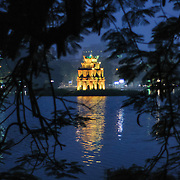 Turtle Tower (also known as Tortoise Tower on a small island in Hoan Kiem Lake in the historical center of Hanoi, Vietnam. The lights of the tower are on and reflected on the water, with the image framed by the branches of a tree on the shore.