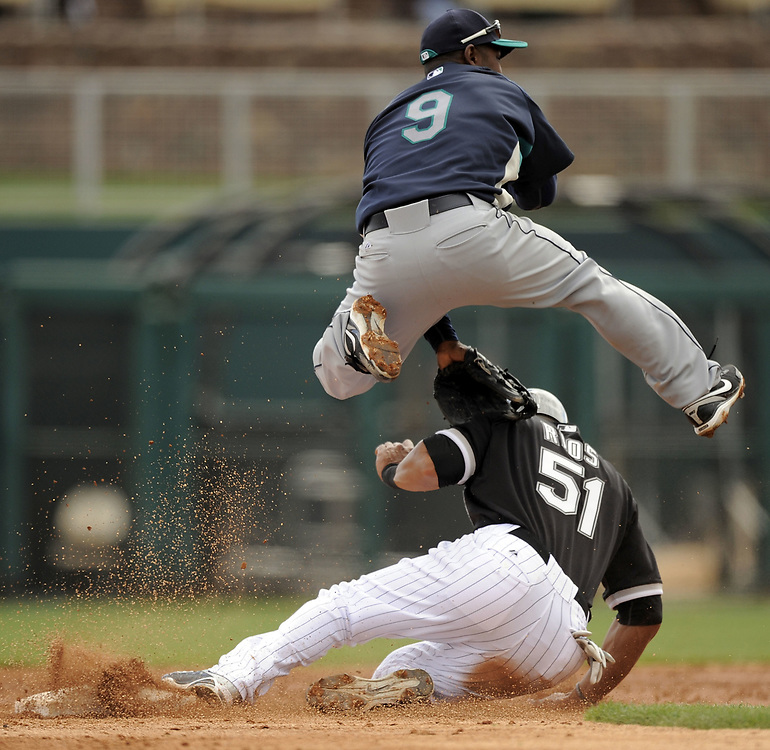 GLENDALE, AZ - MARCH 8:  Chone Figgins #9 of the Seattle Mariners leaps over a sliding Alex Rios #51 of the Chicago White Sox on March 8, 2010 at The Ballpark at Camelback Ranch in Glendale, Arizona. (Photo by Ron Vesely)